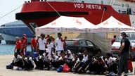 "FILE - Migrants sit on the ground after disembarking from Vos Hestia ship of NGO ""Save the Children"" in the Sicilian harbor of Augusta, Italy, Aug. 4, 2017."