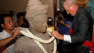 Walter Timoshuk, right, president of Norton Simon Museum of Art in Pasadena, California, places flowers onto a 10th century Cambodian sandstone statue returned from the United States during a handover ceremony at the Council of Ministers in Phnom Pen