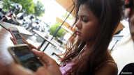 Online activist Thy Sovantha, 19, (L) and her friend use their mobile phones and social media in a cafe in Phnom Penh, Dec. 11, 2014.