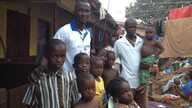 Daddy Hasan Kamara stands outside his Freetown, Sierra  Leone home with family members.