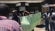 """A Zimbabwean protests against the newly introduced bond notes, which he calls """"fake money,"""" in Harare, Nov. 30, 2016. President Robert Mugabe introduced the new currency to ease the country's almost year-long cash shortage problem. (S. Mhofu/VOA)"""