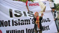 FILE - A woman releases a dove as a symbol of peace during a rally against the Islamic State group, in Jakarta, Indonesia, Sept. 5, 2014.