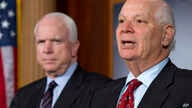 FILE - Sen. Ben Cardin, right, holds a news conference with Sen. John McCain during a media availability on Capitol Hill in Washington, Dec. 6, 2012.