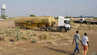 FILE - Two men walk near the Paloch oil fields in Upper Nile State, the site of an oil complex and key crude oil processing facility in the north of the country near the border with Sudan. The area hosts the sole pipeline export route. Fighting in So
