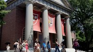 People are led on a tour on the campus of Harvard University in Cambridge, Mass