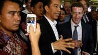 Indonesian President-elect Joko Widodo, center, speaks with Facebook CEO Mark Zuckerberg, right, during their visit to a market in Jakarta, Indonesia, Oct 13, 2014.