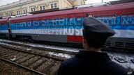 """A railroad worker stands by the first train decorated with letters that read """"Kosovo is Serbian"""" written in twenty languages departing from Belgrade to Mitrovica, Kosovo, Jan. 14, 2017."""