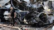 Man inspects site of car bomb explosion in Baghdad's eastern Mashtal neighborhood, Iraq, Nov. 17, 2014.