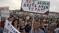 "Protesters hold a placard which reads in Greek ""SOS Moria. Solution now"" referring to the Moria refugee camp, during a protest in the town of Mytilene on the northeastern Aegean island of Lesbos, May 3, 2018."