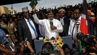 """FILE - Opposition leader Raila Odinga, center, accompanied by lawyers Miguna Miguna, center-left, Tom """"T.J."""" Kajwang, center-right, and politician James Orengo, right, holds a Bible aloft after a mock """"swearing-in"""" ceremony at Uhuru Park in downtown"""