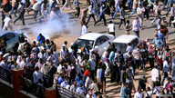 Demonstrators run from teargas lobbed to disperse them as they march along the street during anti-government protests in Khartoum, Sudan, Dec. 25, 2018.