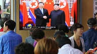 People watch a TV screen showing North Korean leader Kim Jong Un, right, welcoming Chinese President Xi Jinping, at the Seoul Railway Station in Seoul, South Korea, Friday, June 21, 2019.
