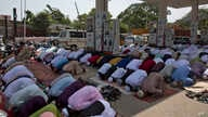 Indian Muslims offer Eid al-Fitr prayers in the shade of a petrol filling station as they join others offering prayers in an open area in Hyderabad, India, Saturday, June 16, 2018.