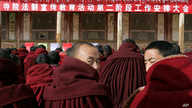 "About 90 monks sit in front of a red banner with white Tibetan and Chinese writing: ""Work Meeting for the Second Phase of Xicang Monastery's Rule of Law Propaganda Education Campaign,"" ahead of the re-education study session at the 200 year old Xica..."
