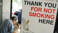 FILE - A man has his lunch behind a poster demarcating a No-Smoking zone in Singapore