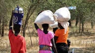 Women and girls walk back after getting food in Bentiu, a 38 kilometers (24 miles) journey using a path through the bush for fear of being attacked on the main road.