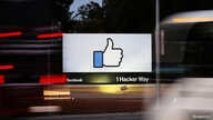 FILE - The entrance sign to Facebook headquarters is seen through two moving buses in Menlo Park, California, Oct. 10, 2018.