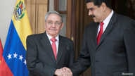 FILE - Cuba's Raul Castro (L) shakes hands with Venezuela's Nicolas Maduro in Caracas, Venezuela, March 5, 2018.