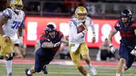 "UCLA quarterback Austin Burton (12) runs during an NCAA college football game against Arizona, Sept. 28, 2019. A bill signed Monday in California will allow student athletes to use their ""name, image, or likeness"" to earn compensation."