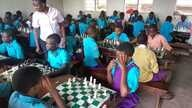 Children in slums of Kampala learning  how to play chess.
