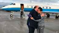 This photo provided by U.S. Embassy Switzerland,  Edward McMullen greets Xiyue Wang in Zurich, Switzerland on Saturday, Dec. 7, 2019.