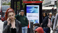 (FILES) In this file photo taken on April 29, 2019, pedestrians use their mobile phones near a Huawei advert at a bus stop in…