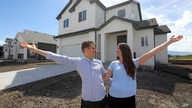 In this April 27, 2019, photo, millennials Andy and Stacie Proctor stand in front of their new home in Vineyard, Utah.