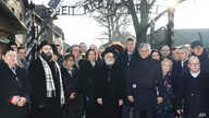 Rabbi Menachem Margolin, second left, the head of the European Jewish Association officials and lawmakers of the Parliament of Europe and Jewish leaders stand at the gate leading to the former Nazi German death camp of Auschwitz in Poland, Jan. 21, 2020.