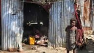 A child stands in front of a makeshift home in the Ma Drapo camp. (Matiado Vilme/VOA Creole)