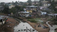 Kids jump on tires over a sewage in a slum in Freetown, Sierra Leone, December 16, 2014. REUTERS/Baz Ratner  (SIERRA LEONE -…