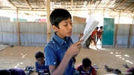 FILE PHOTO: A child reads a book in a makeshift school run by Rohingya teachers in Kutupalong refugee camp in Cox's Bazar,…