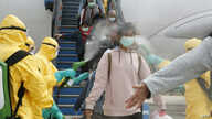 Officials in full protective gear disinfect Indonesian students upon the arrival at Hang Nadim international airport in Batam, following their evacuation from Wuhan, China, due to the coronavirus outbreak. (photo released by Indonesian Embassy)