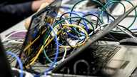 Picture of wires plugged on laptop computers taken as people work on January 22, 2019 in Lille during the 11th International…