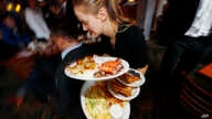 A waitress fights to deliver plates of breakfast through local Republicans gathered to watch the inauguration of Donald Trump, Jan. 20, 2017, in Denver.