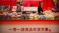 "Clerks stand at a display of goods at a ""Belt and Road Products New Year's Marketplace"" at a shopping mall in Beijing, Friday,…"