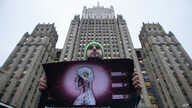 Andrei Nikolayev, an activist of the Green Alternative party, protests outside the Foreign Ministry headquarters building, in the background, to call on officials to do more to prevent the spread of the coronavirus, in Moscow, Russia,  Jan. 24, 2020.