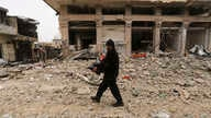 A man carries his belongings through a street destroyed in recent bombings by the Syrian government forces in the town of…