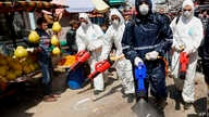 Workers wearing protective gear spray disinfectant as a precaution against the coronavirus, at the main market in Gaza City.