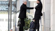 Men keep their distance whilst talking on the street in Milan, Italy, March 4, 2020.