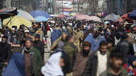 Afghans walk through a crowded market in Kabul, Afghanistan, Feb. 22, 2020.