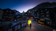 A pedestrian looks at an illuminated map board in the empty streets of the Alpine resort of Zermatt, Switzerland, amid the spread of the COVID-19, March 18, 2020.