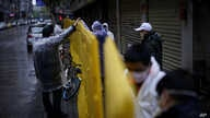 Workers wearing face masks repair barriers built up to block buildings from a street in Wuhan, Hubei province.