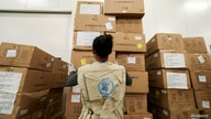 A World Food Program (WFP) worker arranges relief packages at a warehouse designated to the United Nations for humanitarian aid…