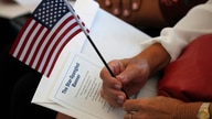 FILE - A soon-to-be U.S. citizen candidate holds an American flag and the words to The Star-Spangled Banner before the start of a naturalization ceremony at the U.S. Citizenship and Immigration Services field office in Miami, Florida, Aug. 16, 2019.