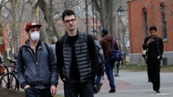 FILE - A student wearing a mask to protect against the coronavirus walks with others at Harvard University, before the school moved its classes to online-only, in Cambridge, Massachusetts, March 10, 2020.