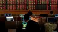 FILE - Traders are seen in front of a screen with mostly red trading figures, at Thailand's Stock Exchange, in Bangkok, March 13, 2020.