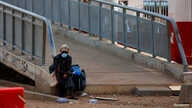 A woman rests on a footbridge, as Ghana enforces partial lockdown in the cities of Accra and Kumasi to slow the spread of the coronavirus disease (COVID-19) in Madina neighborhood of Accra, March 31, 2020.