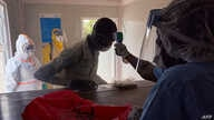 A suspected the COVID-19 coronavirus patient's temperature is measured as he is admitted at the isolation ward of Ministry of…