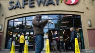 Reginald Conyers, a traveling busker, plays the trumpet outside of a Safeway grocery store, in Oakland