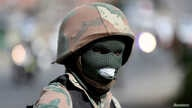 FILE PHOTO: A member of the South African National Defence Force looks on during a patrol in an attempt to enforce a nationwide…